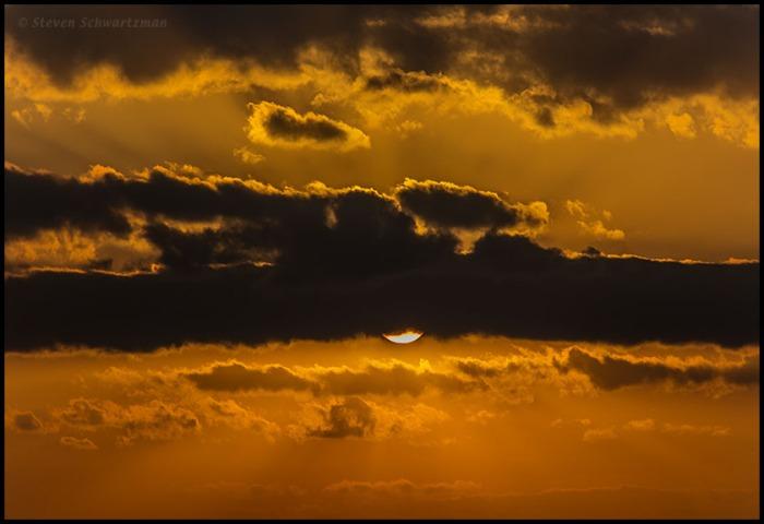 Sun Emerging Below Sunset Clouds 6969